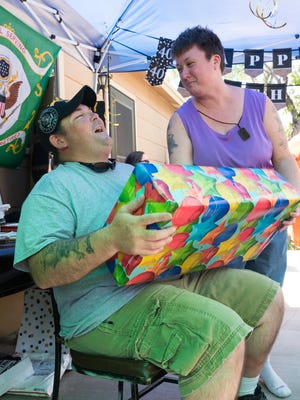 Jeffrey and Darlene Fleming enjoy a good laugh as she hands him a special present during the celebration Saturday, July 29, 2017.