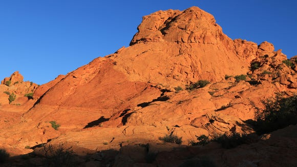 Cliffs along the Arch Trail in the Red Cliffs Desert Reserve are ablaze with light shortly after sunrise.