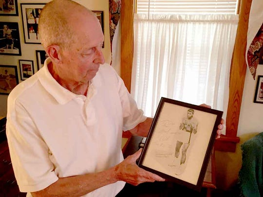 Sports columnist and broadcaster Don Scott holds an autographed photo of Muhammad Ali he acquired when the legendary boxer visited Hershey in 1972.
