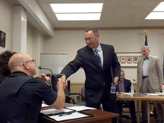 Joseph Morales, one of nine applicants for a vacant seat on Lebanon City Council, shakes hands with police Chief Todd Breiner and Mayor Sherry Capello (hidden) after being interviewed by Chairman Wiley Parker (standing rear) and other council members Wednesday night.