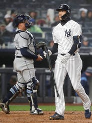 New York Yankees' Giancarlo Stanton, right, walks to the dugout after striking out for the fifth time in a baseball game against the Tampa Bay Rays in New York, Tuesday, April 3, 2018. Rays catcher Jesus Sucre (45) prepares to return the ball to the pitcher. (AP Photo/Kathy Willens)