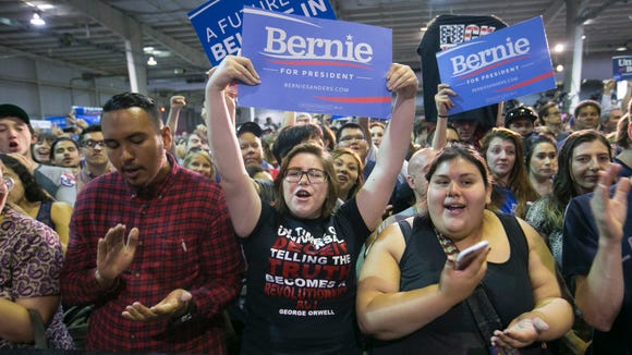 Bernie Sanders supporters Bryan Hurtado, (from left) Elizabeth Ferrendelli and Victoria Anaya, all of Glendale cheer for Democratic Presidential candidate Bernie Sanders speaks during his rally at the Arizona State Fairgrounds in Phoenix on Saturday, March 19, 2016.