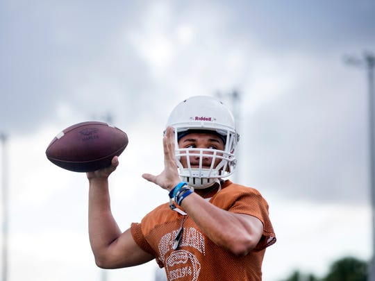 Jordan Persad-Tirone, a senior quarterback for the Naples High School varsity football team, passes the football during practice at Staver Field on Tuesday, August 1, 2017.