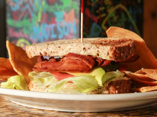 A sandwich of bacon, lettuce, tomato and avocado on