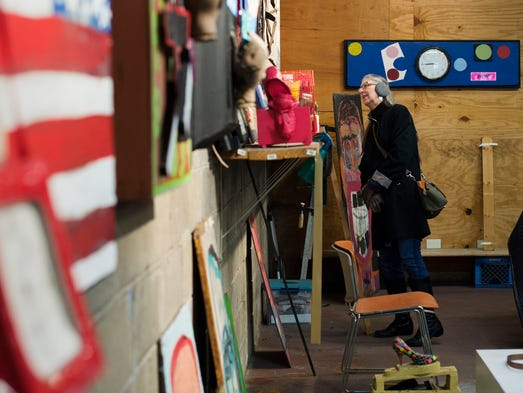 Tina Herzberg of Sylvan Lake looks at artwork during