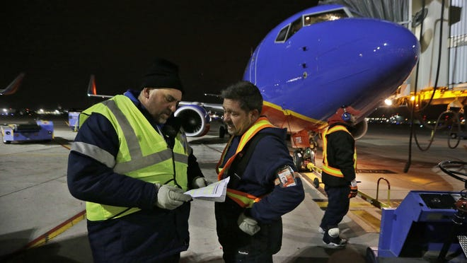 Southwest Airlines ramp supervisor Steve Belch, left, confers with ground crewman Dillard Blue after a mechanical glitch developed on the early morning originator flight waiting for departure from the gate behind them, at Love Field in Dallas.