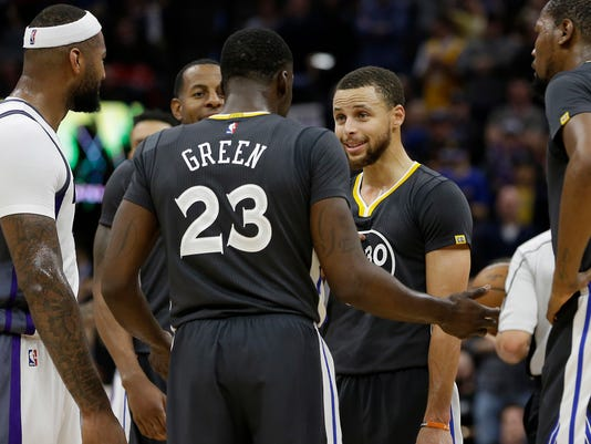 Golden State Warriors guard Stephen Curry, second from right, talks with teammate Draymond Green after he was called for a technical foul during the third quarter of an NBA basketball game against the Sacramento Kings Saturday, Feb. 4, 2017, in Sacramento, Calif. The Kings won in overtime 109-106. (AP Photo/Rich Pedroncelli)