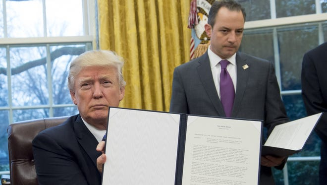 President Trump holds up an executive order withdrawing the US from the Trans-Pacific Partnership after signing it alongside White House Chief of Staff Reince Priebus in the Oval Office Monday.