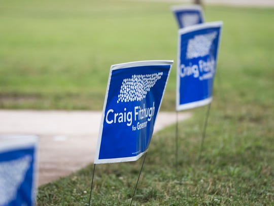 Signs are posted in the grass at the Knox Blue Dot