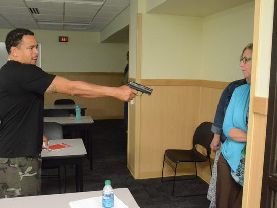 Officer Damon Young confronts hiding KCC employees during a training Monday on responding to active shooters.