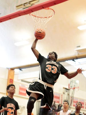Belleville's Calvin Blaydes (33/F) goes up for the shot during Romulus' 66-47 win in the district basketball playoff game on Monday at Westland Glenn.