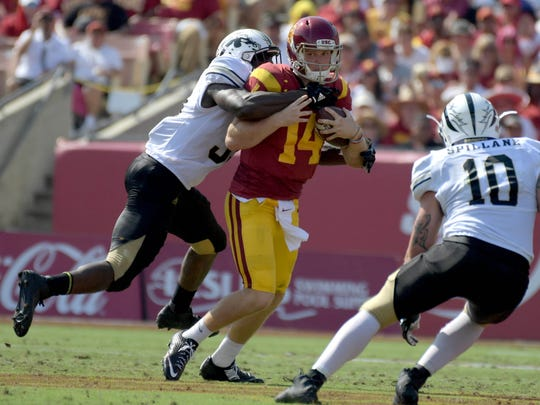 Southern California Trojans quarterback Sam Darnold (14) is sacked by Western Michigan Broncos defensive lineman Eric Assoua (33) during a NCAA football game at Los Angeles Memorial Coliseum.