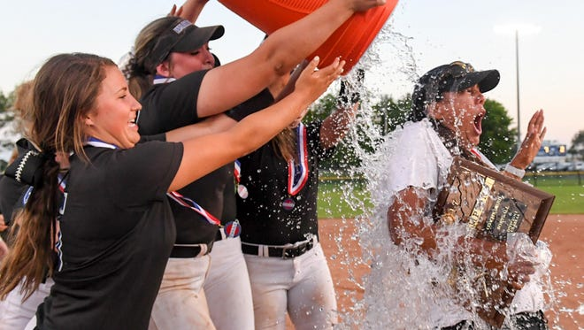 Christian Academy of Knoxville's Paige Simpson (5) and Emma Webb (10) are assisted by other team members as they pour water on head coach Dayna Carter at the conclusion of their 2017 Class AA State Girls' Softball Championship game against McNairy County, Friday, May 26.