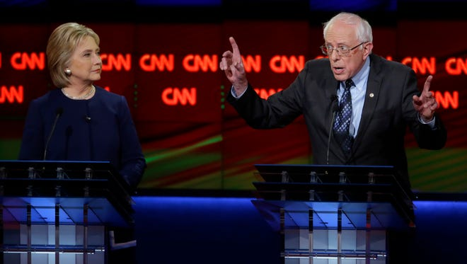 Bernie Sanders argues a point as Hillary Clinton listens during the Democratic debate on March 6, 2016, in Flint, Mich.