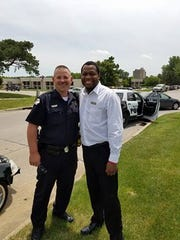 Joe Carter stands with West Des Moines Police Officer Shawn Miller after he assisted him with his disabled car.