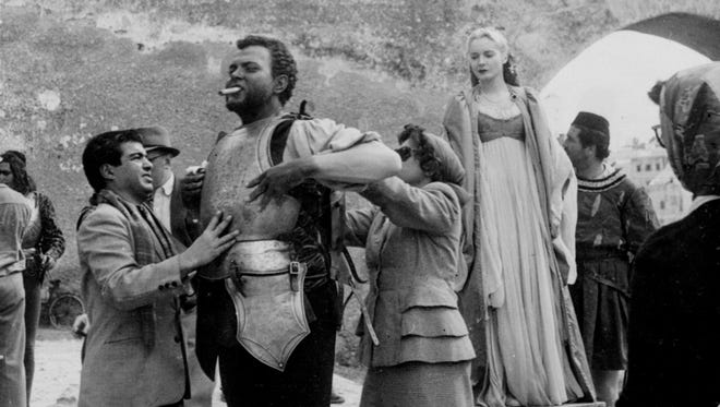 "Orson Welles, a cigar in his mouth, has his armor adjusted before filming a scene from ""Othello,"" which he was making in Safi, French Morocco. At right is Suzanne Cloutier, who played Desdemona."
