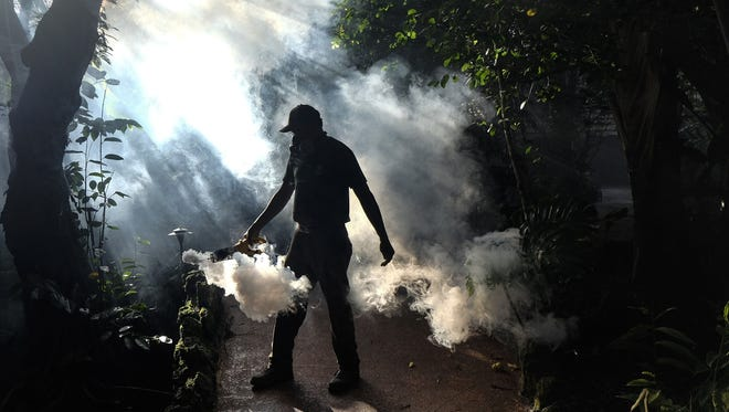 Groundskeeper Fran Middlebrooks uses a blower to spray pesticide to kill mosquitoes as Miami-Dade County fights to control the Zika virus outbreak.