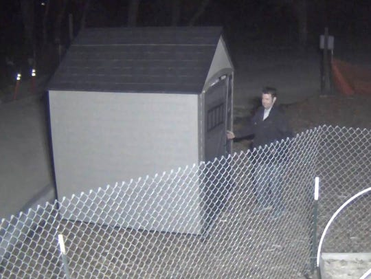 A surveillance image shows a man breaking into a garden