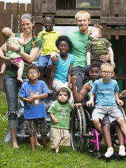 """Katie and Gregg Eichhorn, with their eight children at their home in Price Hill. All of them are adopted (one is pending) and seven have special needs. Gregg Eichhorn said, """"You have to be intentional about being a father. Having kids is a blessing, a joy."""""""