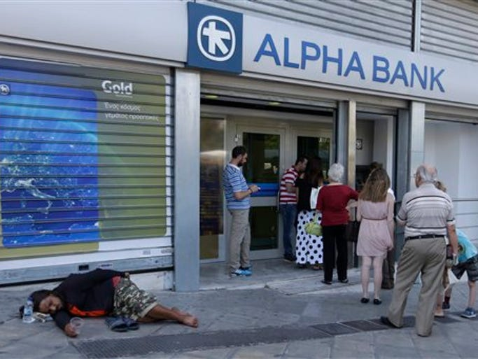 People stand in a queue to use an ATM of a bank as