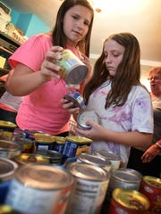 Sara Artley, 14, of Fredericksburg, and Haley Blair, 11, of Jonestown, sort cans of donated food. The Ono United Methodist Church youth group helped out at the Jonestown Outreach Pantry on Wednesday, July 6, sorting, packing and shelving donated goods.