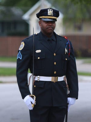Des Moines Honor Guard Sgt. Bernell Edwards stands at attention for a 21-gun salute.
