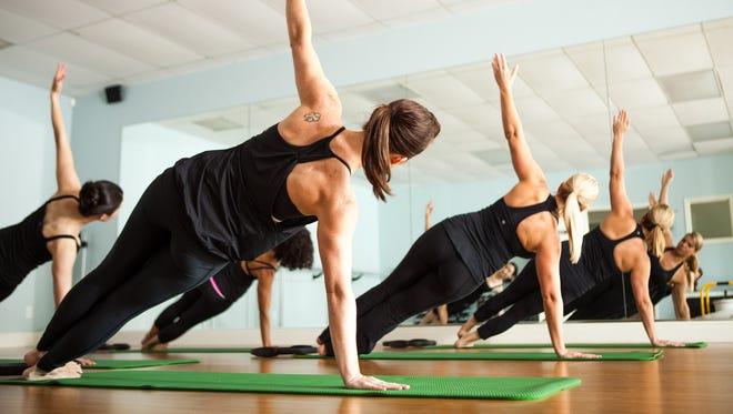 Participants perform side  planks during Floor Barre at Beyond Motion Studio in Naples.