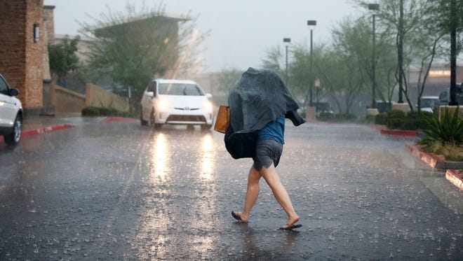 A shopper makes for cover in a monsoon rain storm on July 9, 2018, in Scottsdale.