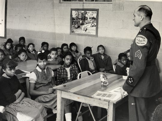 A State Highway Patrol sergeant talks about road safety with children at Carver Elementary School in 1954.