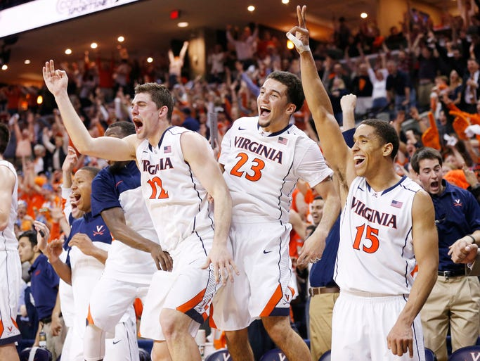 Virginia guards Joe Harris (12), London Perrantes (23), and Malcolm Brogdon (15) celebrate on the bench in the final seconds against the Syracuse Orange at John Paul Jones Arena. The Cavaliers won 75-56 and clinched the ACC regular season title.