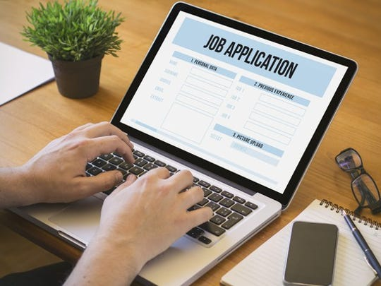 Person filling out job application on laptop