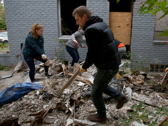 Nic Cantaloupe, 31, of Sterling Heights, makes another trip with garbage from the backyard of an abandoned home on Joann Street in Detroit on Sat., Oct. 3, 2015. Cantaloupe was part of Team Depot, Home Depot's volunteer program that had more than 30 people helping in various Detroit neighborhoods with the volunteer based community group I Believe In The D.