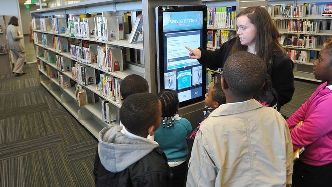 Ann Beth Prater, a teacher at Priest Lake Christian Academy, explains the interactive catalog to her students Tuesday at the grand opening of the new Southeast Davidson County Library.