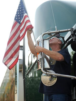 Jim Swallen secures a flag on the side of the truck carrying the memorial Wednesday evening.
