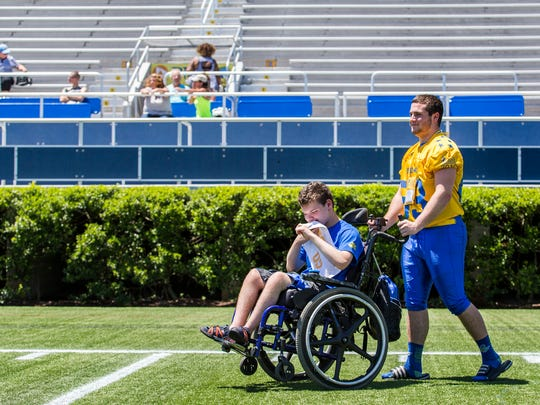 Brady Abraham pushes Sean Burke around the field during the Blue-Gold Football media day at Delaware Stadium in Newark on Sunday afternoon.