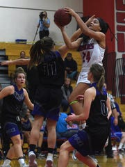 Reno's Kaitlynn Biassou (24) drives to the basket while being guarded by McQueen's Kaila Spevak (11) during their basketball game at Reno on Feb. 9, 2018.