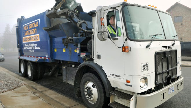 A West Central Sanitation truck collects garbage.