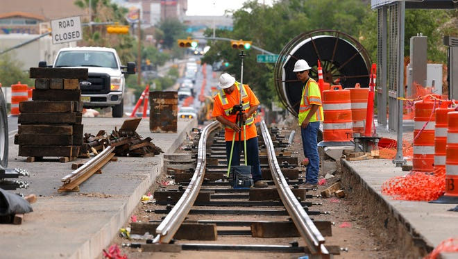 Work crews continue to install rails for the new streetcar project along Oregon Street near Glory Road. Here, surveyors working on the project prepare to begin some plotting work Tuesday afternoon.