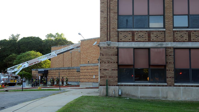 Firefighters from multiple area agencies work on controlling a fire at the former Walter French Academy on Thursday in south Lansing.