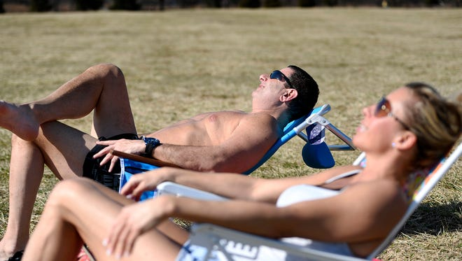 Andrew Levi, left, of River Vale and Terri Levitsky of Leonia sunbathe during an unseasonably warm winter day in Overpeck County Park in Leonia on Feb. 21, 2018.