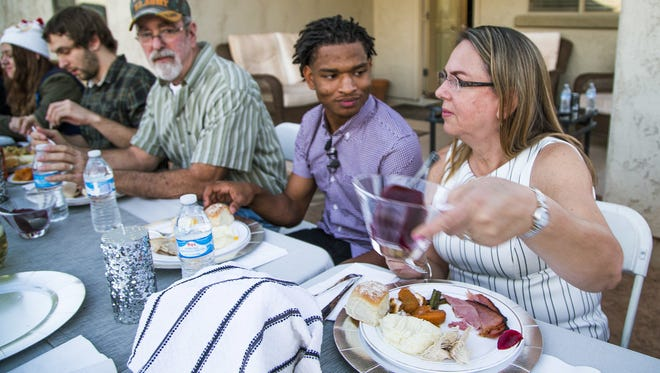 In this Thursday, Nov. 24, 2016 photo, Jamal Hinton, center, and Wanda Dench, right, and her family and friends, have Thanksgiving dinner at Wanda's home, in Mesa, Ariz.  Dench, who accidentally texted Hinton, a stranger, an invitation to Thanksgiving dinner made good on her offer, greeting the teen visitor with a hug and an oven full of food after their story swept through social media.  (Tom Tingle/The Arizona Republic via AP)