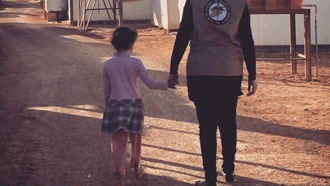 Susan Edlibi, a first-year medical student at Michigan State University, walks with a child through the Zaatari refugee camp.