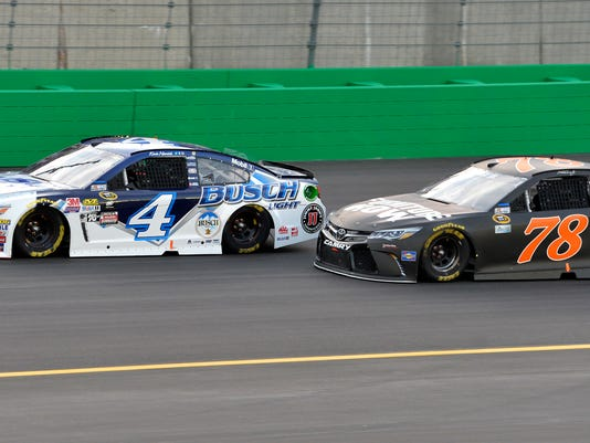 Kevin Harvick (4) attempts to hold off the challenge of Martin Truex Jr. (78) as they head into the first turn during the NASCAR Sprint Cup Series auto race at Kentucky Speedway, Saturday, July 9, 2016 in Sparta, Ky. (AP Photo/Timothy D. Easley)