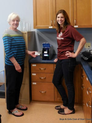 Elfriede Leporte, P.E.O member (left) and Jessica Heck, operations director at the Boys & Girls Club of Door County, demonstrate card identification device