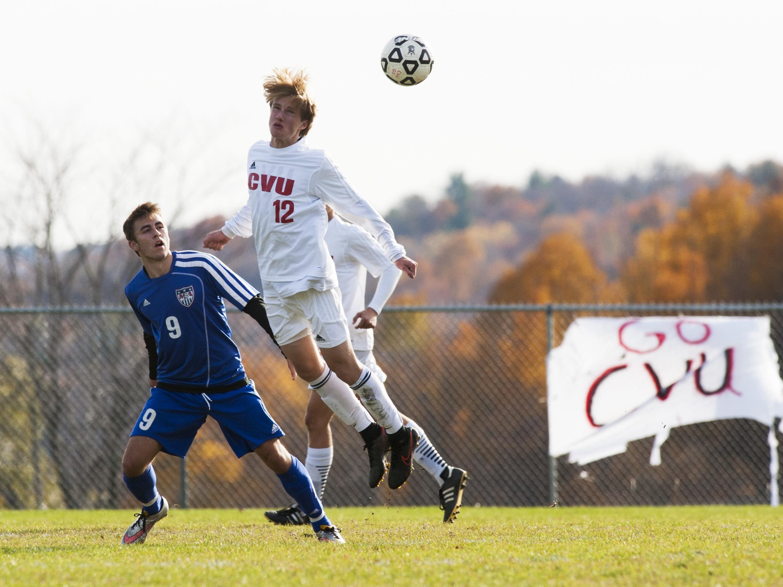 CVU's Joe Parento (12) leaps over Mt Anthony's Carter Bentley (9) to head the ball during the Division I high school boys soccer semifinals Tuesday.