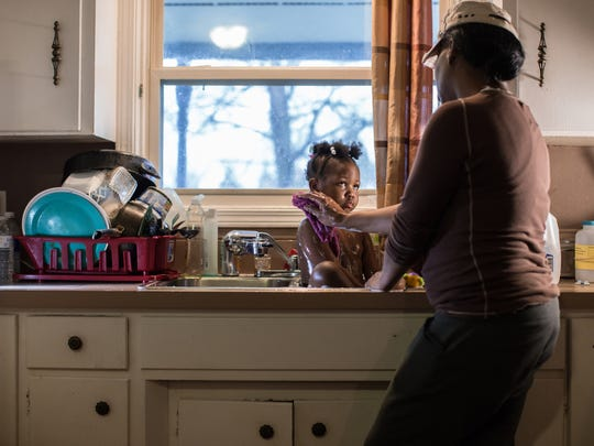 Ivory Gipson, then 44, of Flint is seen washing her