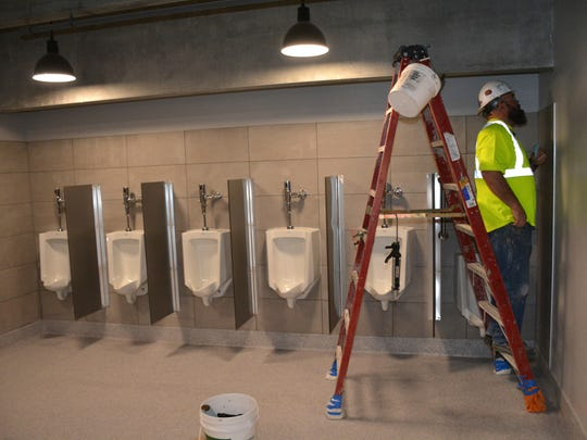 Workers apply the final touches to a rest room on the
