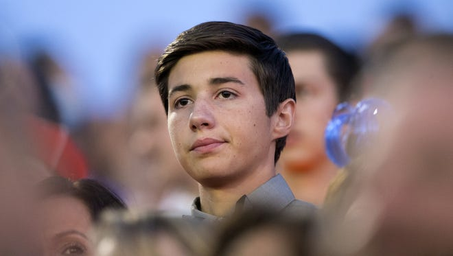Stephen Dwyer, student body president and a member of the Class of 2016 at Dobson High School, sits in the bleachers during Dobson's graduation ceremonies in Mesa on Thursday evening, May 26, 2016. Dwyer had to miss his junior year while undergoing treatment for leukemia. He was some credits short and was not allowed to sit with his class in cap and gown, which he had requested. He had to sit in the bleachers after leading the students in.