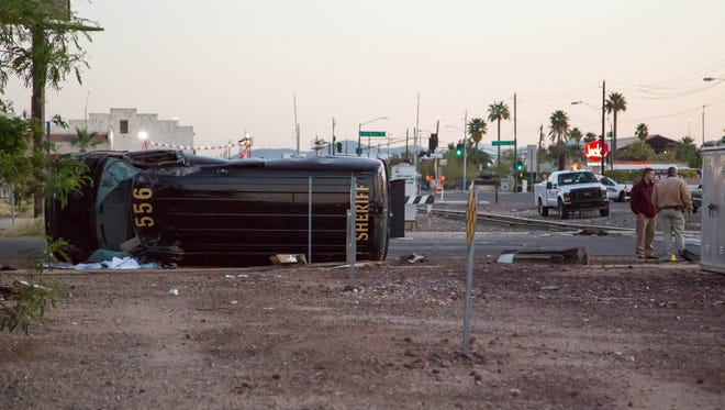 Detention officers had to kick through a window to get out of the transport van that rolled in a collision with a Cadillac on March 24, 2017, in Phoenix.