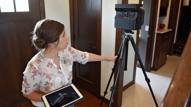 Technician Larissa Gohmann of 360 Real Estate Image positions a Matterport 3-D camera Tuesday, May 3, to create 3-D walkthrough-style images at a new home in Sartell.